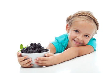 Happy healthy girl with a bowl of blackberries