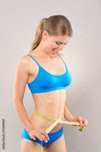 Figure care woman looking at her reduced waist and smiling