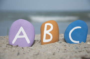 abc on colourful stone letters on the sand