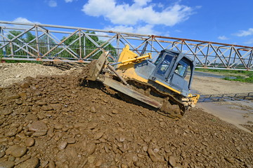 Bulldozer at work to strengthen the shoreline of the river.