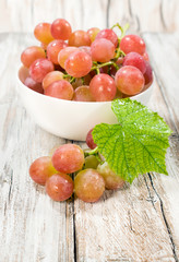 ripe grapes in a white bowl with a leaf