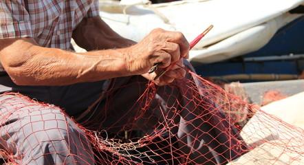 Mani che rammendano la rete da pesca