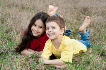 Two smiling kids on the autumn grass
