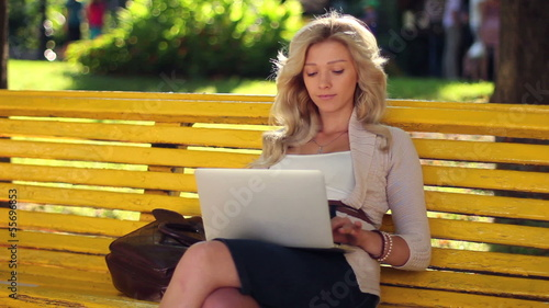 Businesswoman in park typing message to laptop smiling