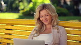 Smiling laughing girl in park with laptop, yellow bench female
