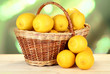 Ripe lemons in wicker basket on table on bright background