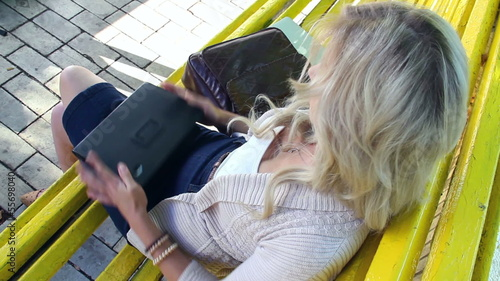 Young woman sets aside tablet pc sitting on yellow bench