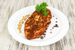 Roasted chicken fillets on white plate, on wooden background