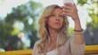 Woman looks at phone taking photo of herself, smartphone mirror