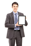 Smiling businessman in suit showing a tablet