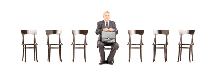 Mature businessman holding briefcase and waiting for interview