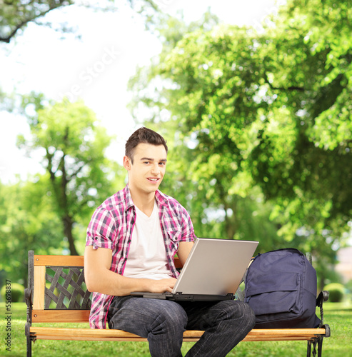 Smiling male student sitting on a bench and working on a laptop