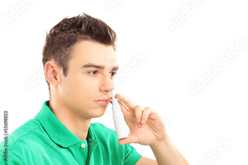 Young man spraying nose drops