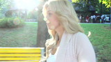 Following beautiful blond woman turns and smiles to camera park