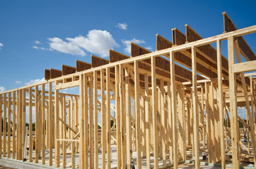 New residential construction home framing against blue sky
