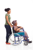 young african woman pushing grandmother on wheelchair