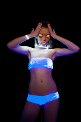 Energetic girl with UV make-up posing at disco