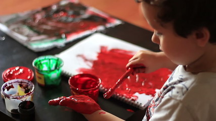 Child paints her hand red watercolor paint