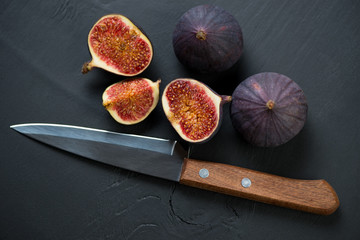 Whole and sliced figs on dark wooden background, view from above