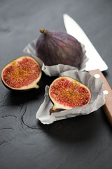Whole and sliced figs on dark wooden background, vertical shot