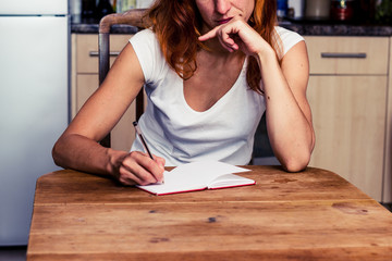 Thoughtful woman writing in her kitchen