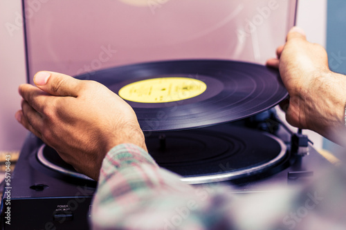 Hands placing record on turntable