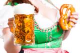 junge Frau im Dirndl mit Bier und Brezn