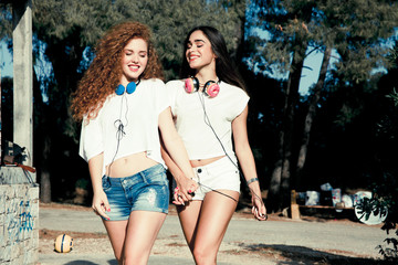 two young girls with headphones walking in a park