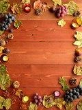 Grapes,fall leaves and pine cone.brown wood background