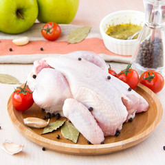 Raw whole small chicken with black pepper and herbs