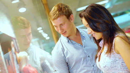 young beautiful couple walking in the store and view items in sh