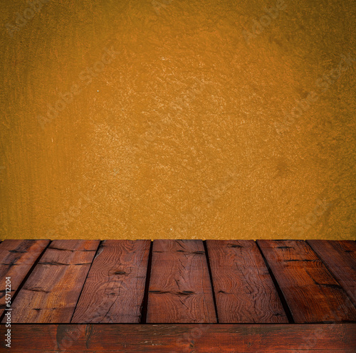 Background with wooden table and grunge orange wall