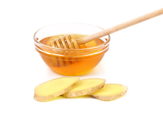 Honey in bowl and a slices ginger root.