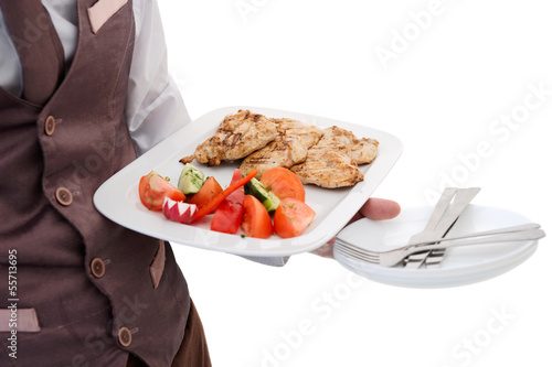 Waiter is offering grilled meat and vegetables
