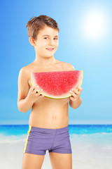 Shirtless kid holding a slice of watermelon on a beach
