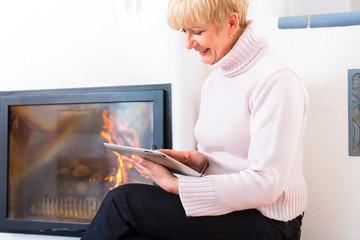 Rentnerin zu Hause vor dem Kamin