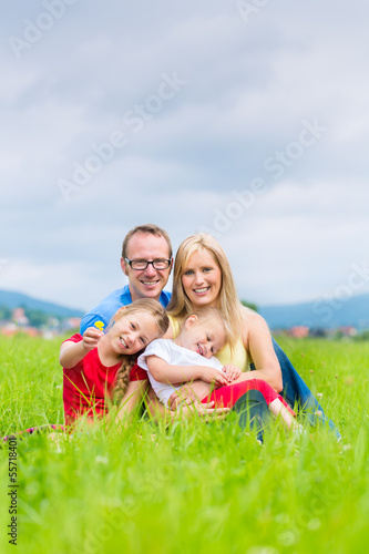 Happy Family outdoors sitting on grass