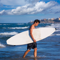 boy surfer holding surfboard caming out from the waves
