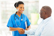 african american medical nurse handshaking with senior patient