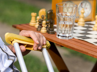 Pensioner with crutches playing chess