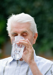 Older man drinking water from glass