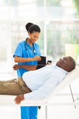 african female nurse measuring senior patient blood pressure