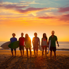 Surfers boys and girls group walking on beach