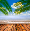 Tropical sea and beach with palm leaves and wooden floor