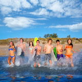 Teenager surfers group running beach splashing
