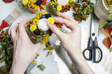 Florist at work. Woman making autumn floral decorations
