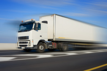 Truck with big white trailer in motion, modified image
