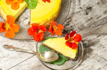Pumpkin cheesecake decorated with fresh flowers on glass plate
