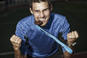 athlete holding a medal in the teeth