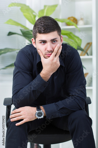 businessman sitting in a chair worried about too much work